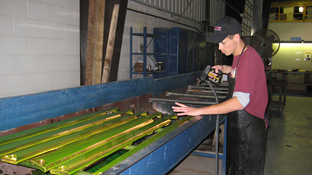 Products undergoing fluorescent LP inspection at rinsing station
